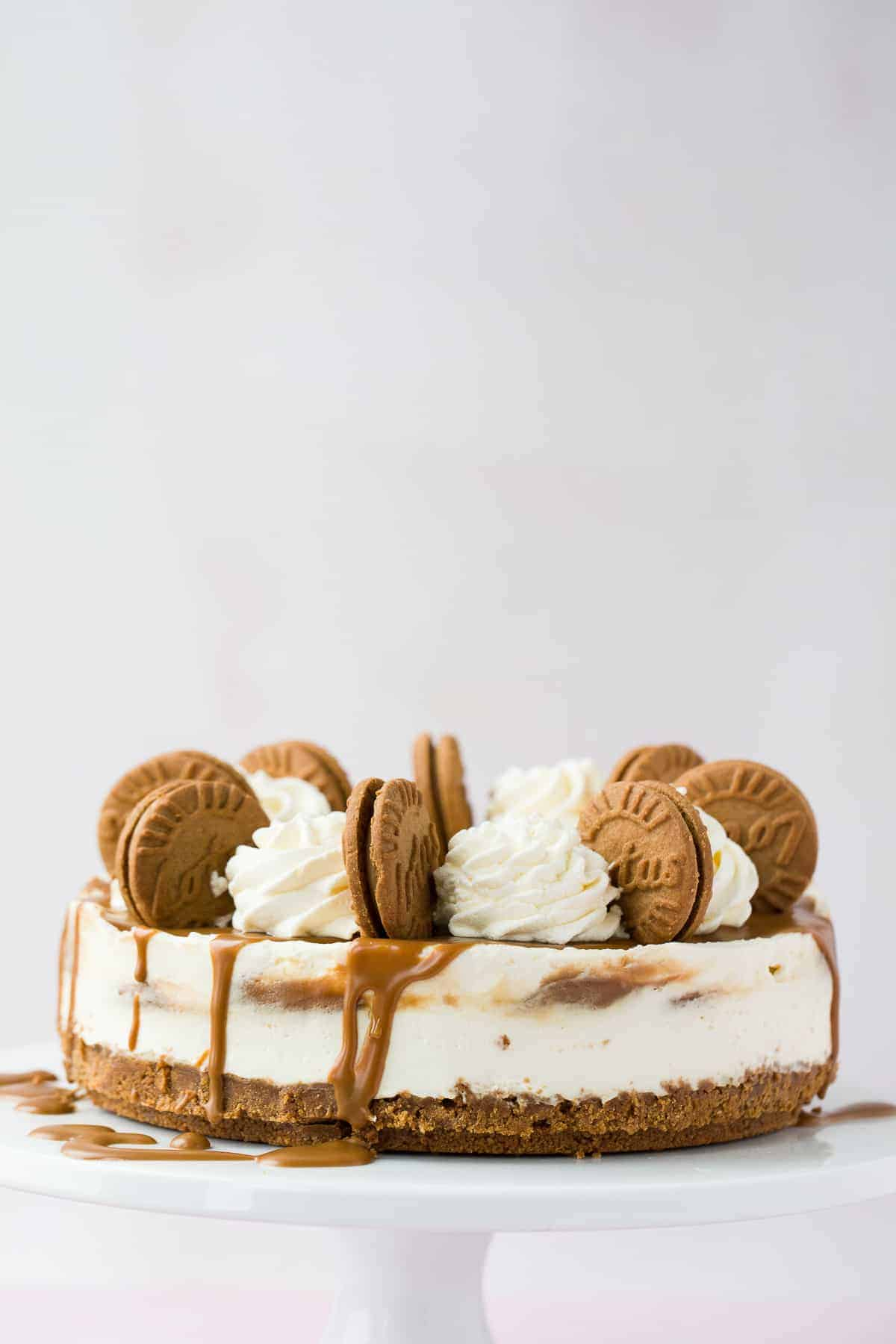 A biscoff flavoured cheesecake on a white cake stand.