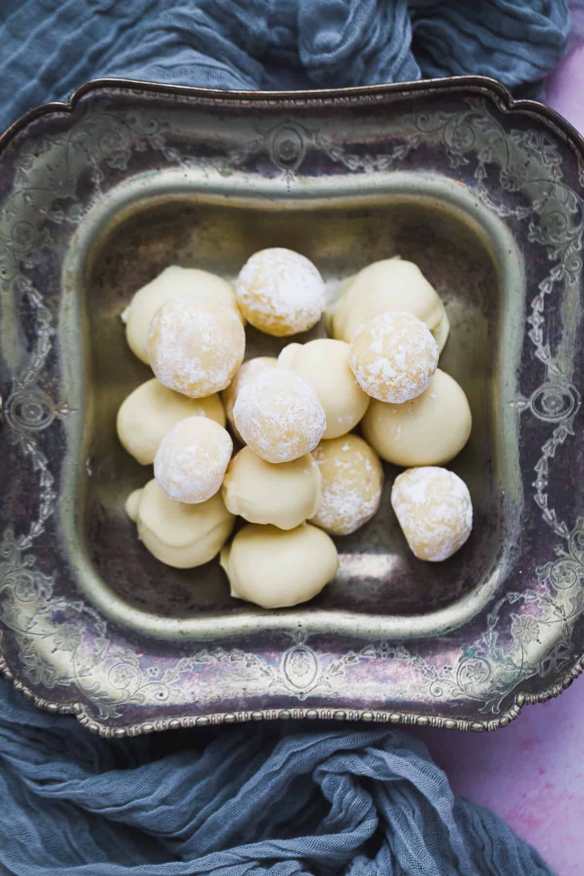 A vintage tray filled with white chocolate and lemon truffles. Half of them have been coated in icing sugar while the other half have been coated in white chocolate.