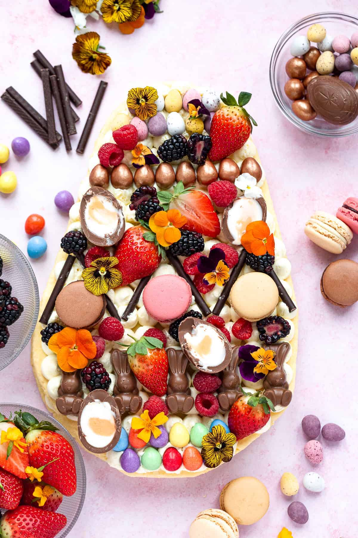 An Easter cookie cake in the shape of a giant Easter egg. It's covered with Easter chocolate, macarons, fresh fruit and edible flowers.