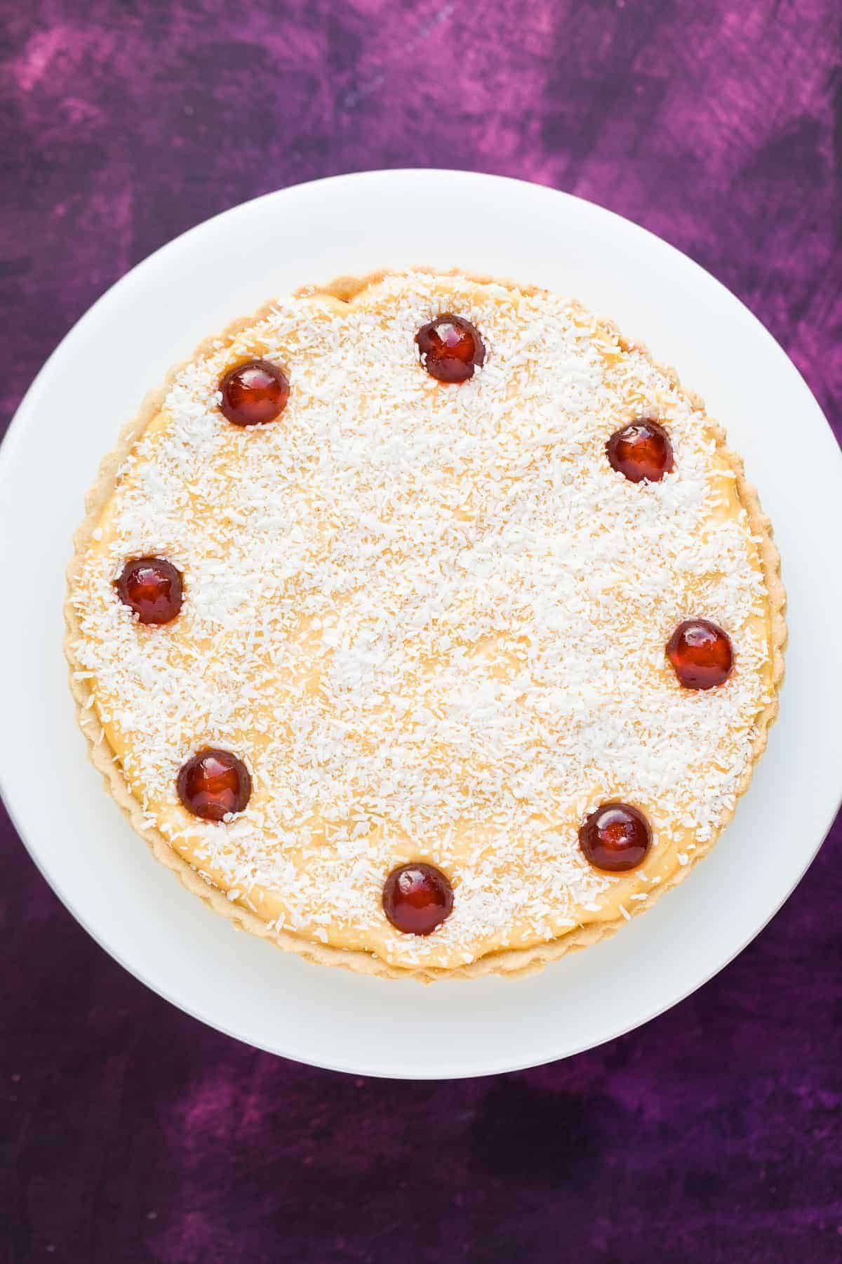 A Manchester tart with sweet pastry, raspberry jam, sliced banana, homemade custard and topped with desiccated coconut and maraschino cherries.
