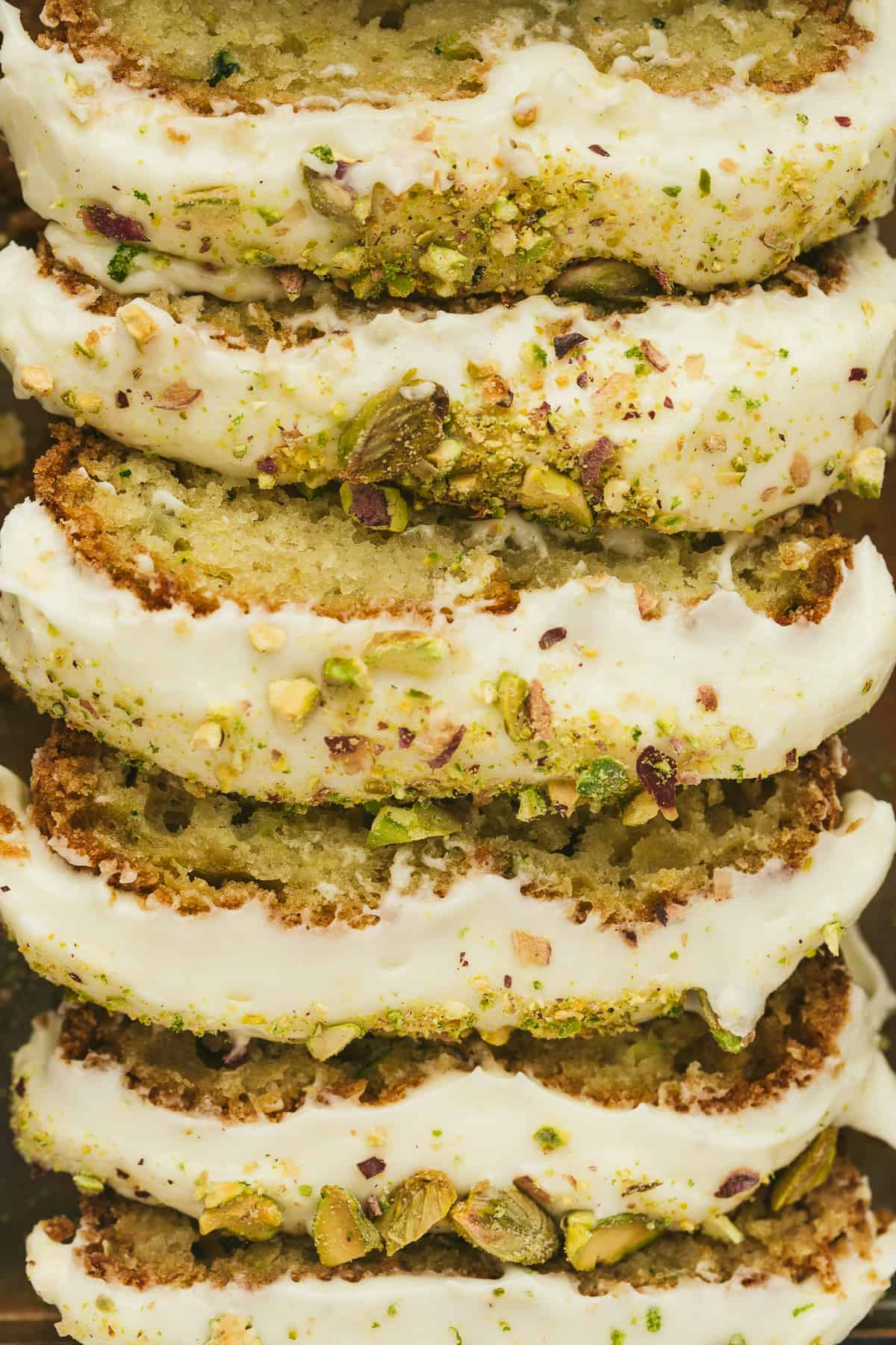 A zucchini cake cut into slices and topped with frosting and chopped pistachios.