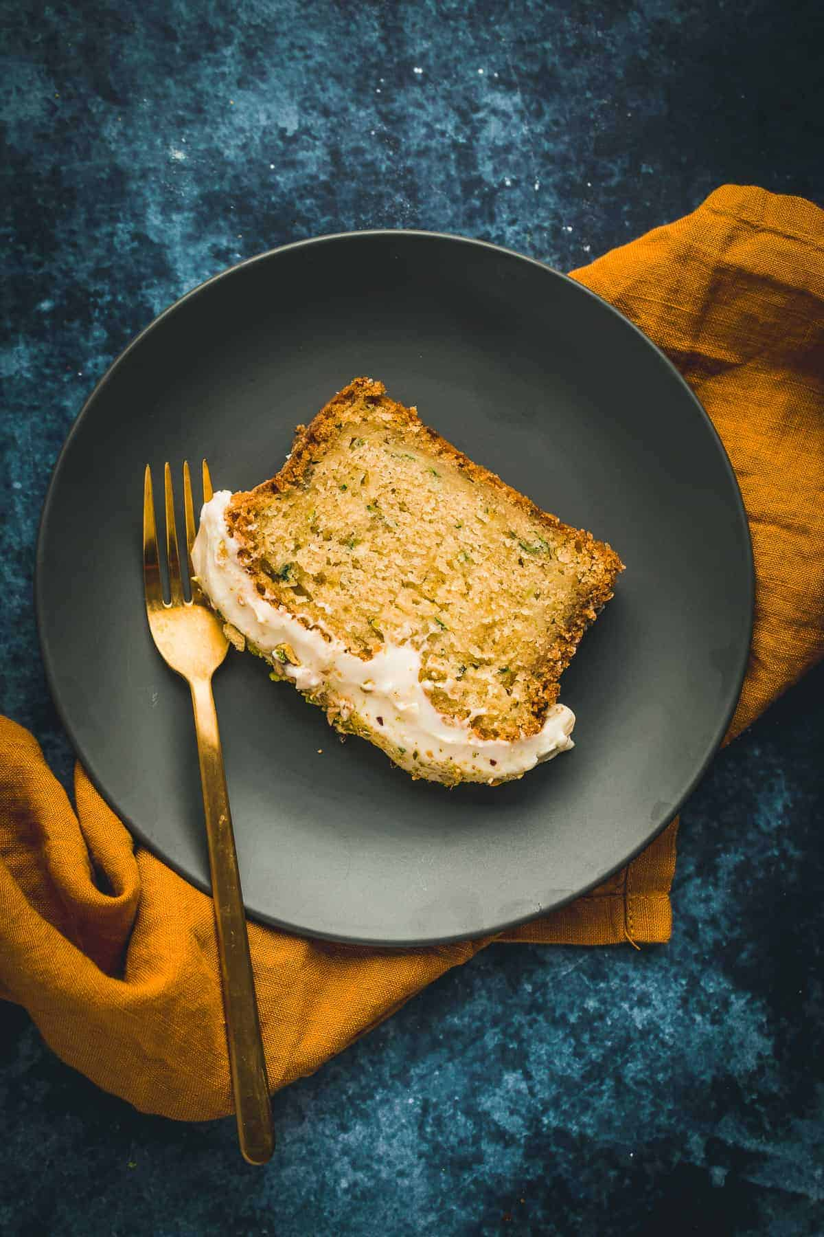 A slice of courgette and lime cake that has been topped with a lime cream cheese frosting.