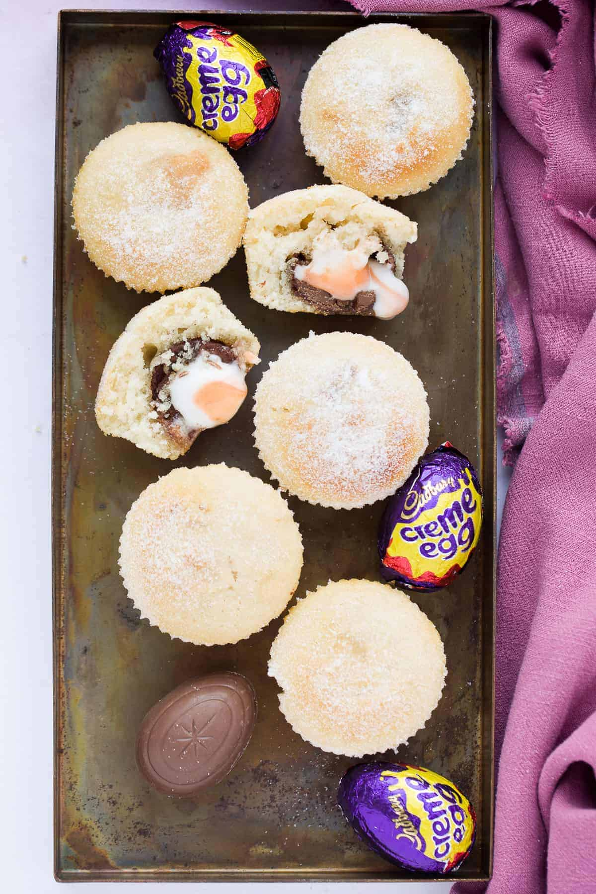 Doughnut muffins with creme eggs on a baking tray.