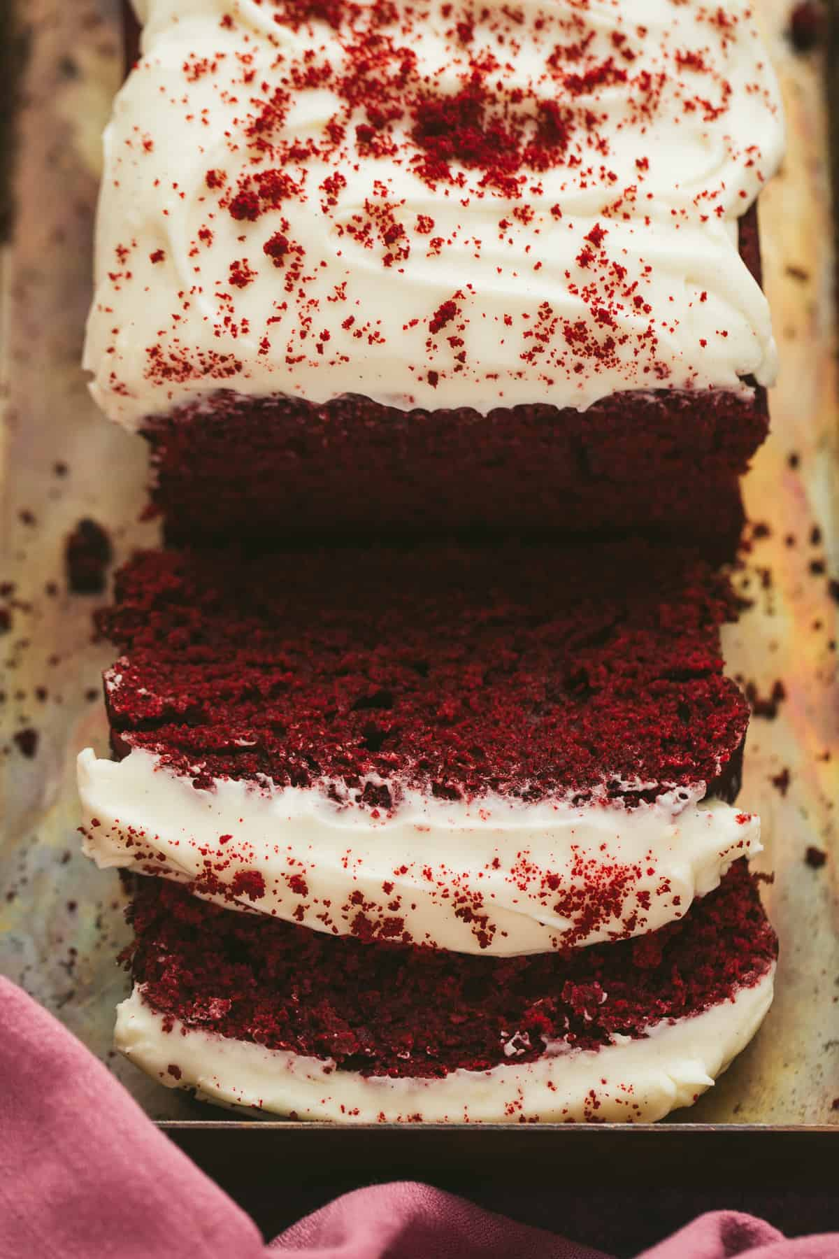 A red velvet loaf cake that has had two slices cut away.