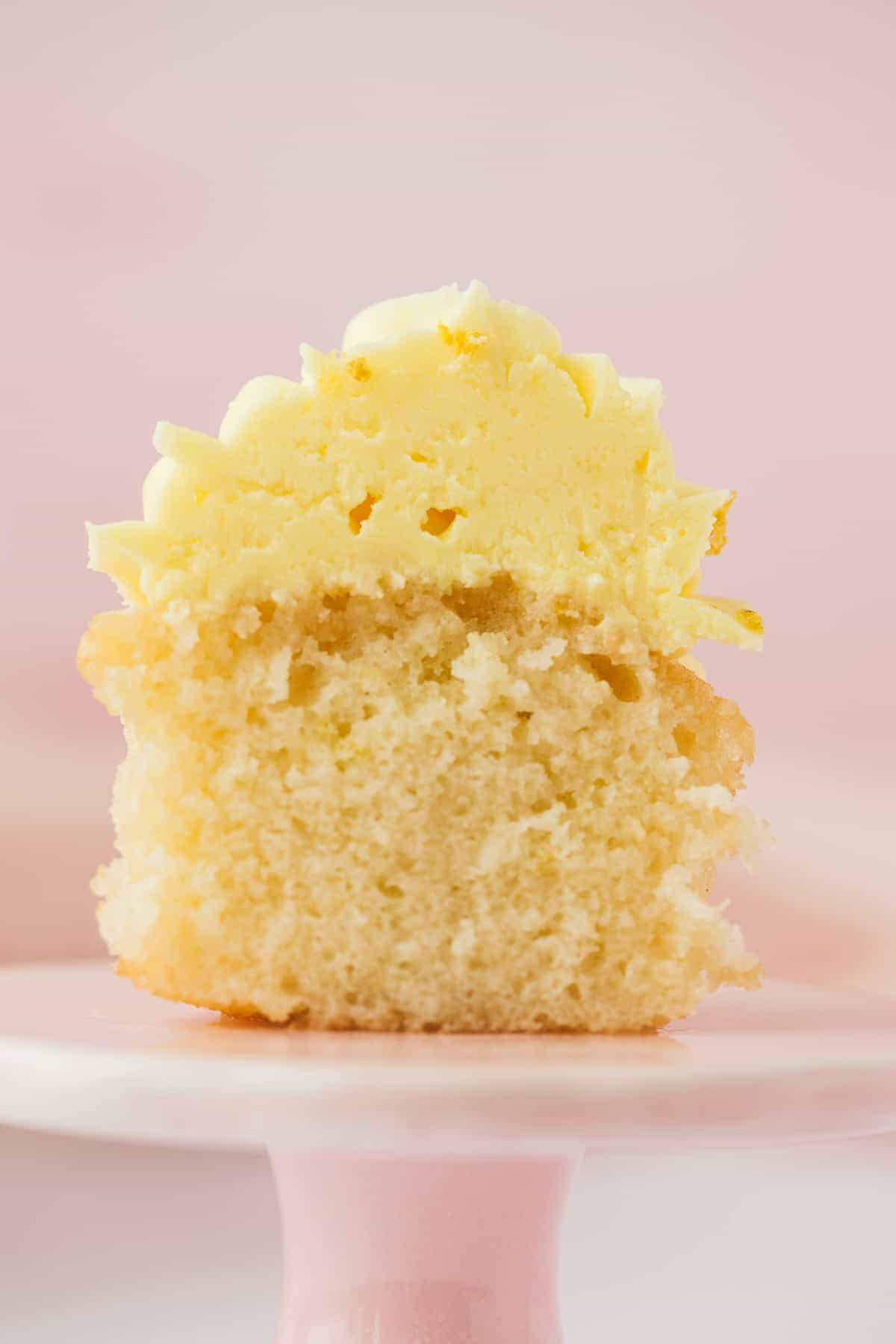 A lemon drizzle cupcake that has been sliced open to reveal it's soft moist centre.