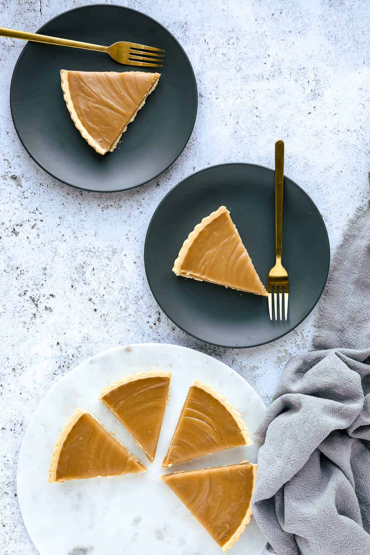 A Butterscotch Tart that has been sliced, there are two pieces on small grey plates and the rest is on a white marble chopping board.