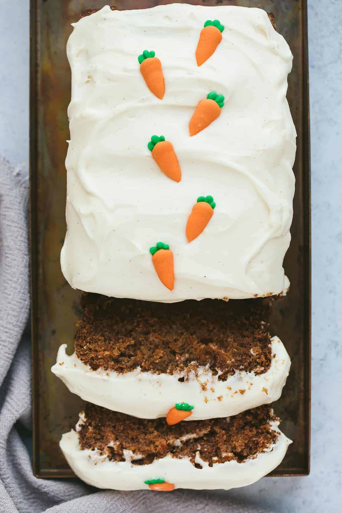 A carrot cake loaf that has two slices cut away. There is a cream cheese frosting on top and tiny fondant carrots.