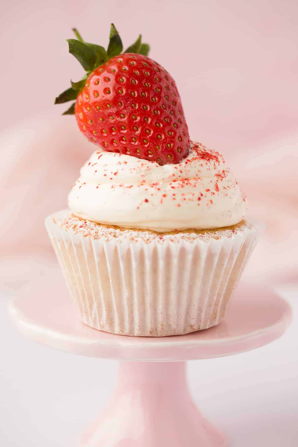 A Victoria Sponge Cupcake with a whipped cream topping and strawberry decoration.