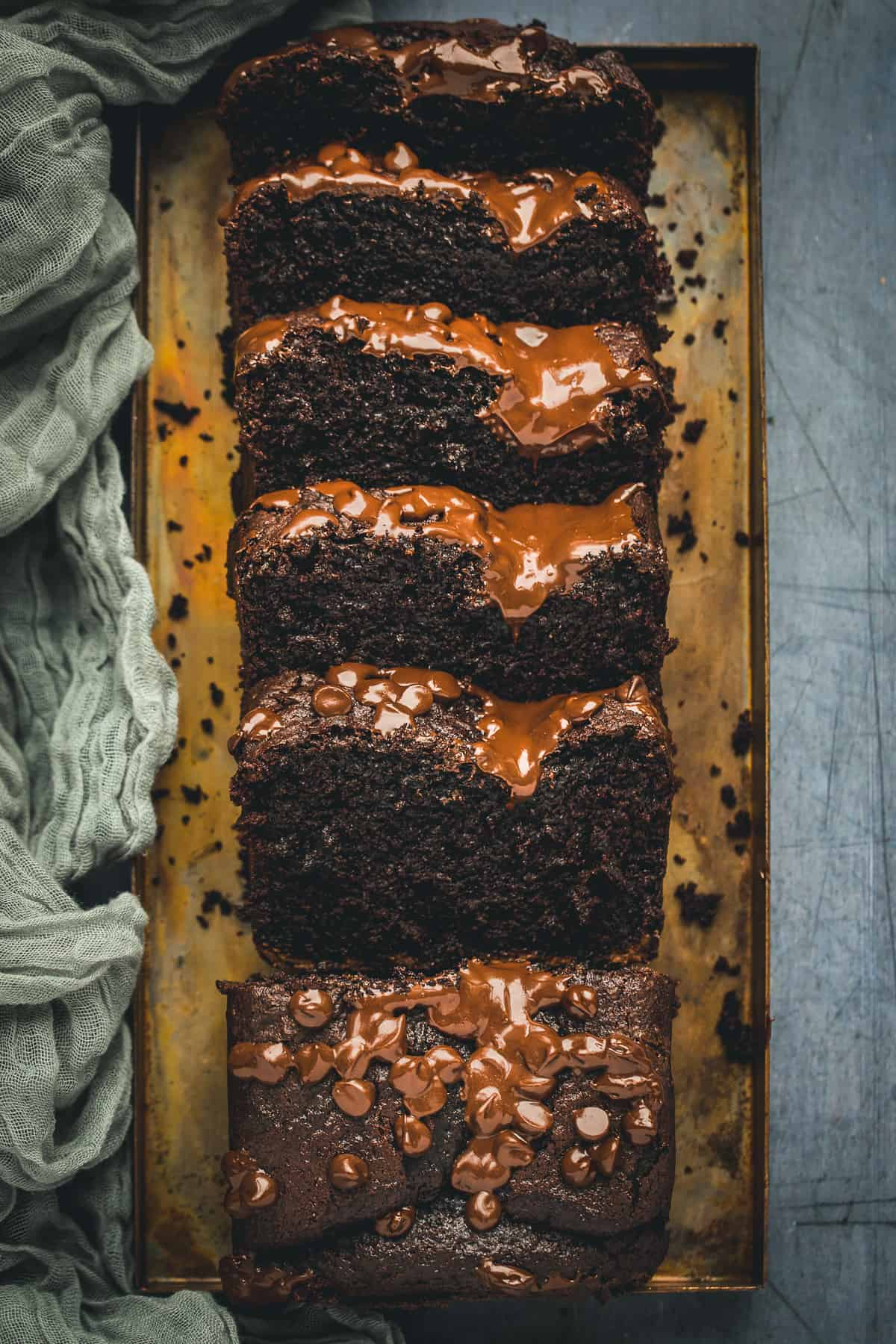 A moist and fudgy chocolate loaf cake that has five large slices cut out of it.