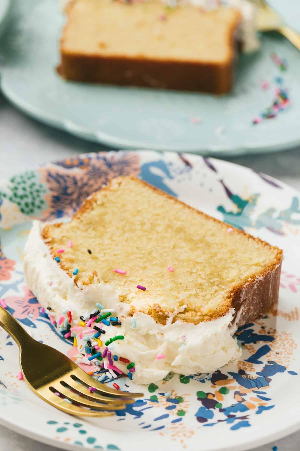 A slice of sponge cake on a patterned plate.