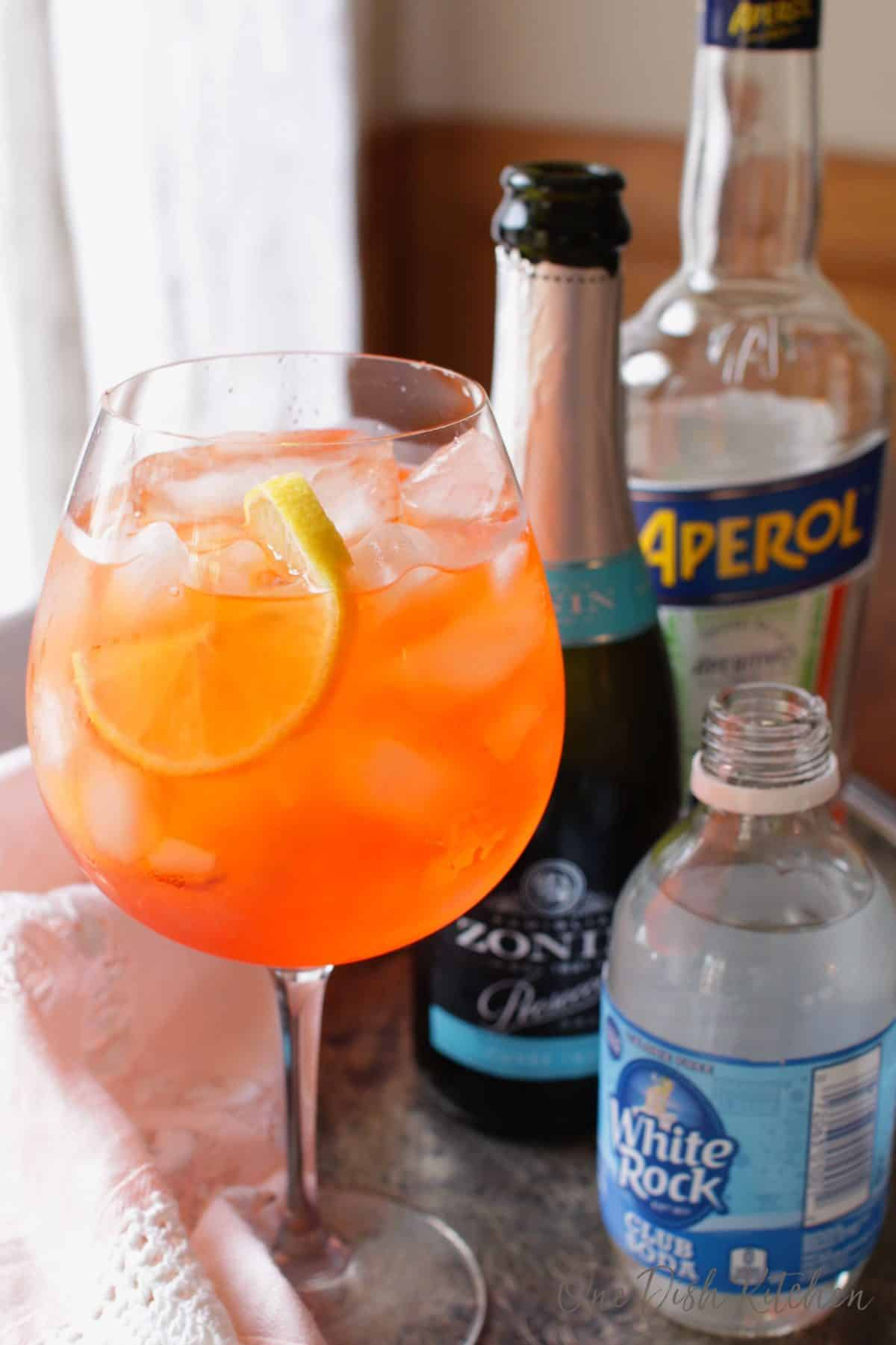 An aperol spritz and a small bottle of champagne, aperol and club soda