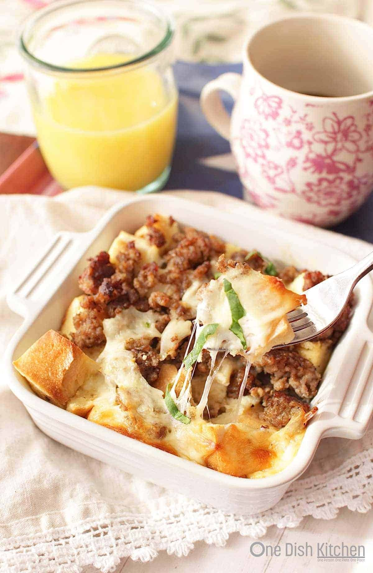 A forkful of breakfast casserole from a small baking dish next to a glass of orange juice and a coffee mug