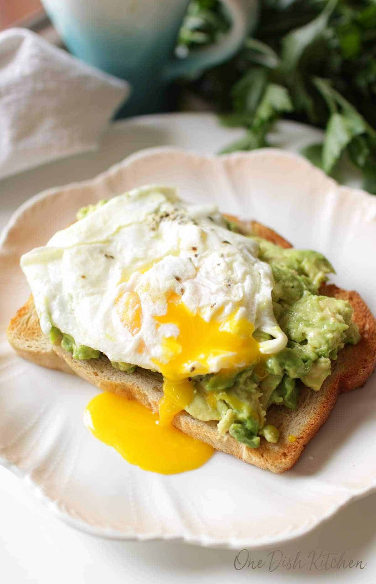 Avocado toast with a runny egg on top on a plate