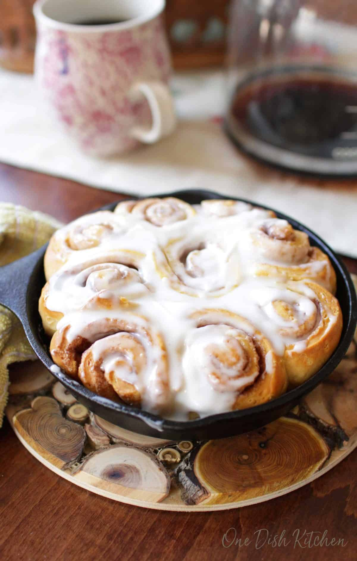 A small skillet of homemade cinnamon rolls topped with frosting on a wooden trivet