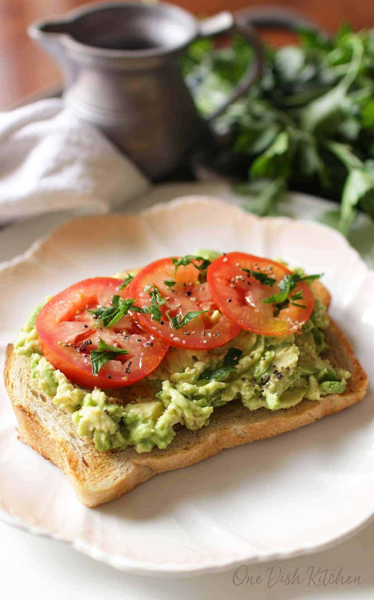 Avocado toast topped with three tomato slices, salt, pepper, and basil on a plate