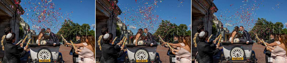Bride and groom with their wedding car under confetti cannons.
