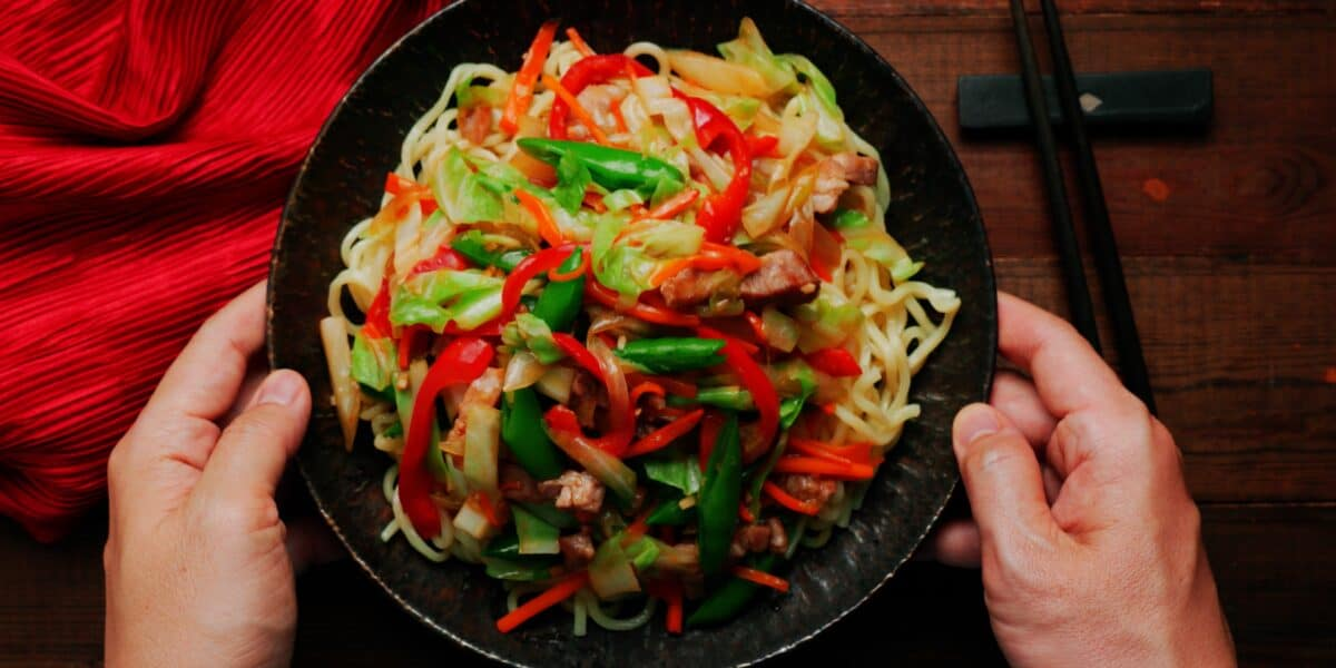 Chop Suey in a dark plate being placed on a dark wood table with a red napkin and chopsticks.