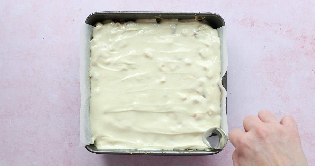 White chocolate being added to the top of a no bake fridge cake.
