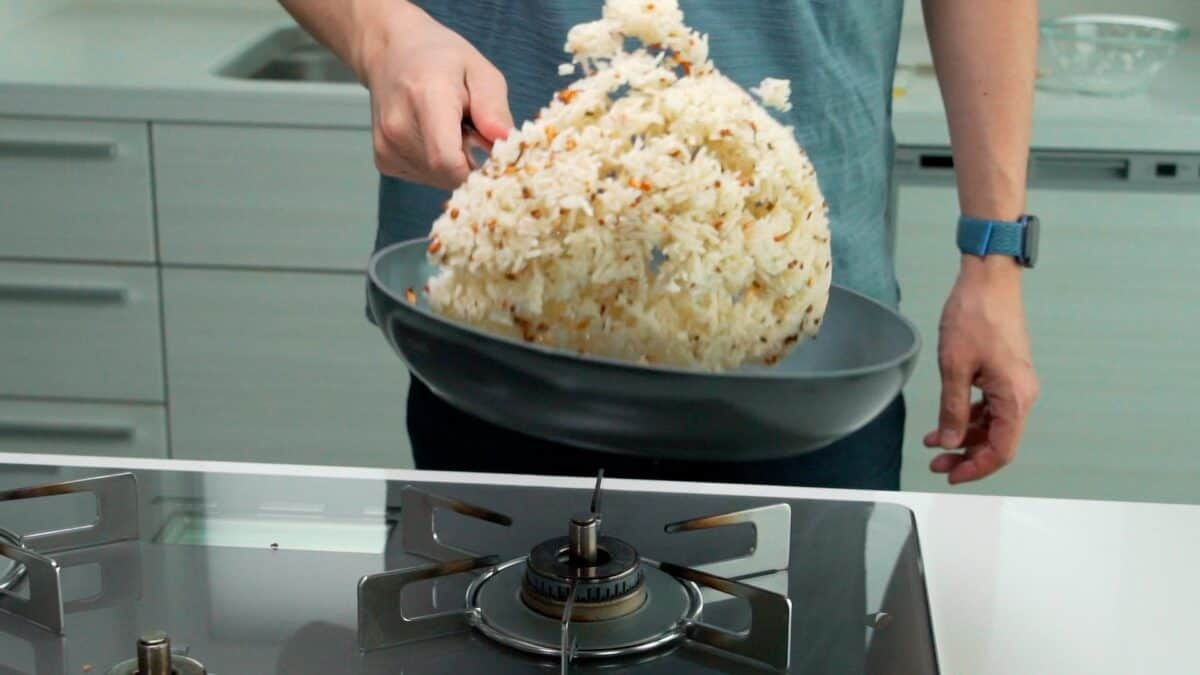 Tossing garlic rice in a pan.