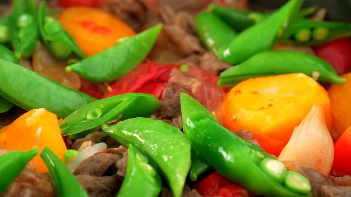 Closeup of finished Nikujaga with snap peas, potatoes, carrots, beef and tomatoes.