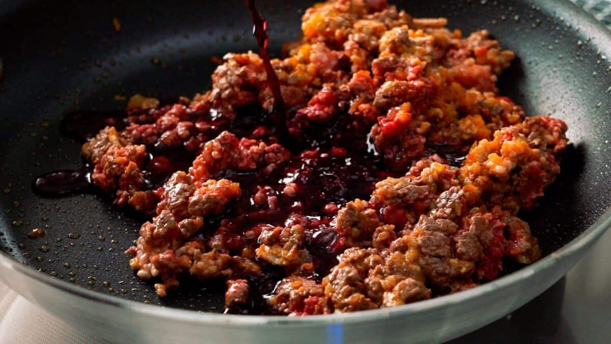 Red wine being added to the meat sauce.