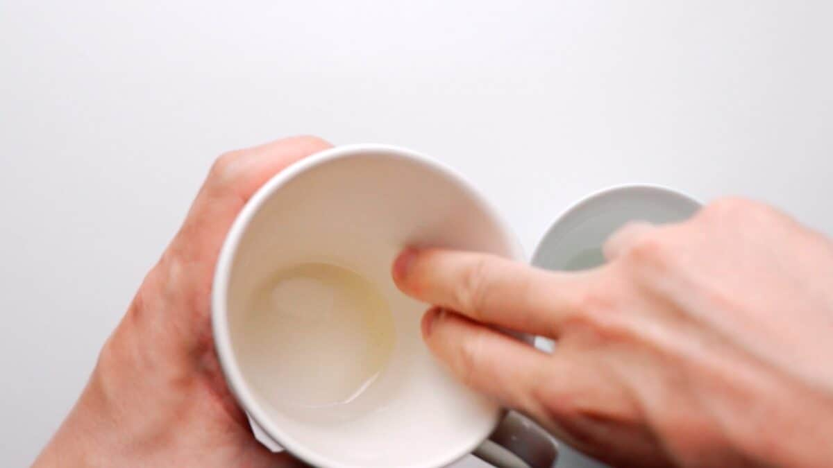 Lining a mug with oil to keep the cake from sticking.