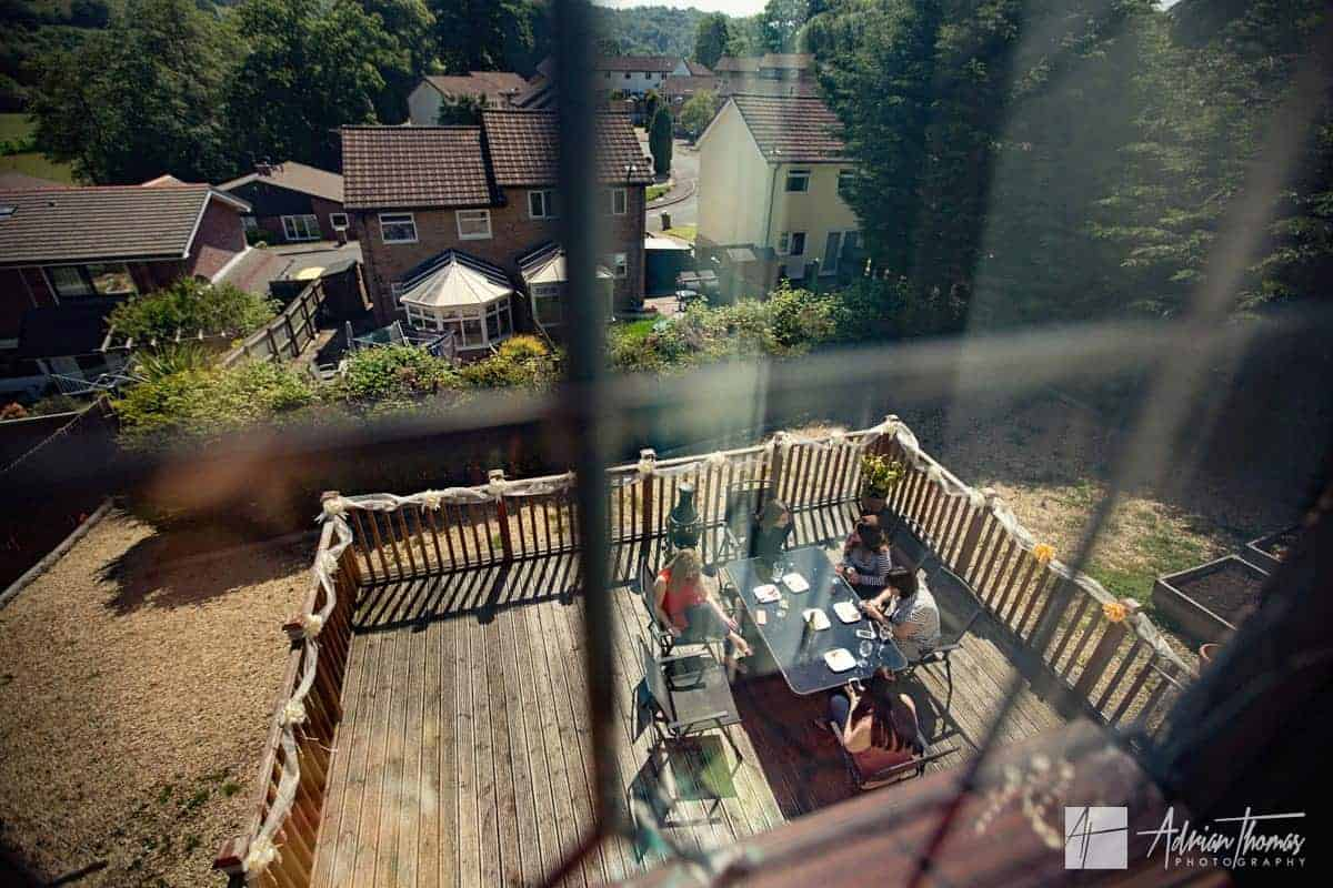 Wedding guests sitting outside house in garden and sun