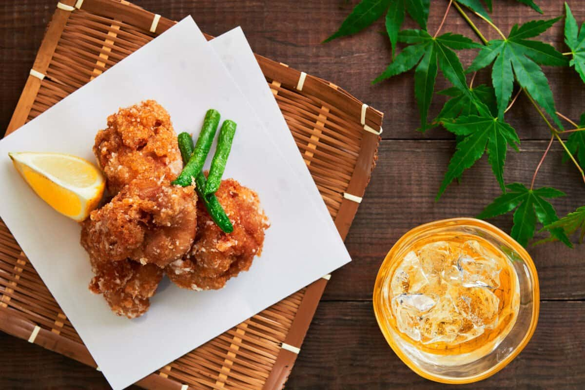 Crispy Chicken Karaage (Japanese Fried Chicken) presented in a basket with Japanese maple leaves and a glass of shochu.