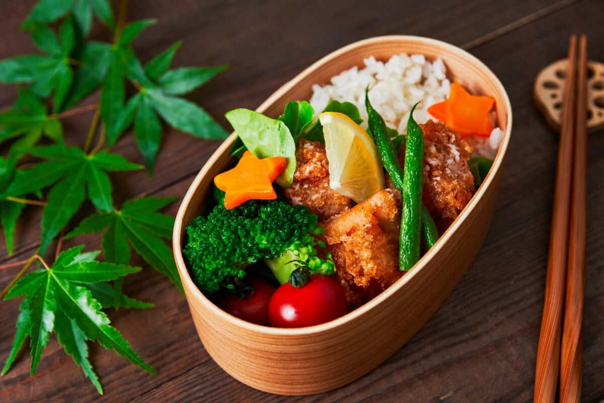Karaage (Japanese fried chicken) in a wooden bento box with rice, lemon, carrots, tomatoes, and broccoli. Karaage is one of the most popular bento items in Japan.