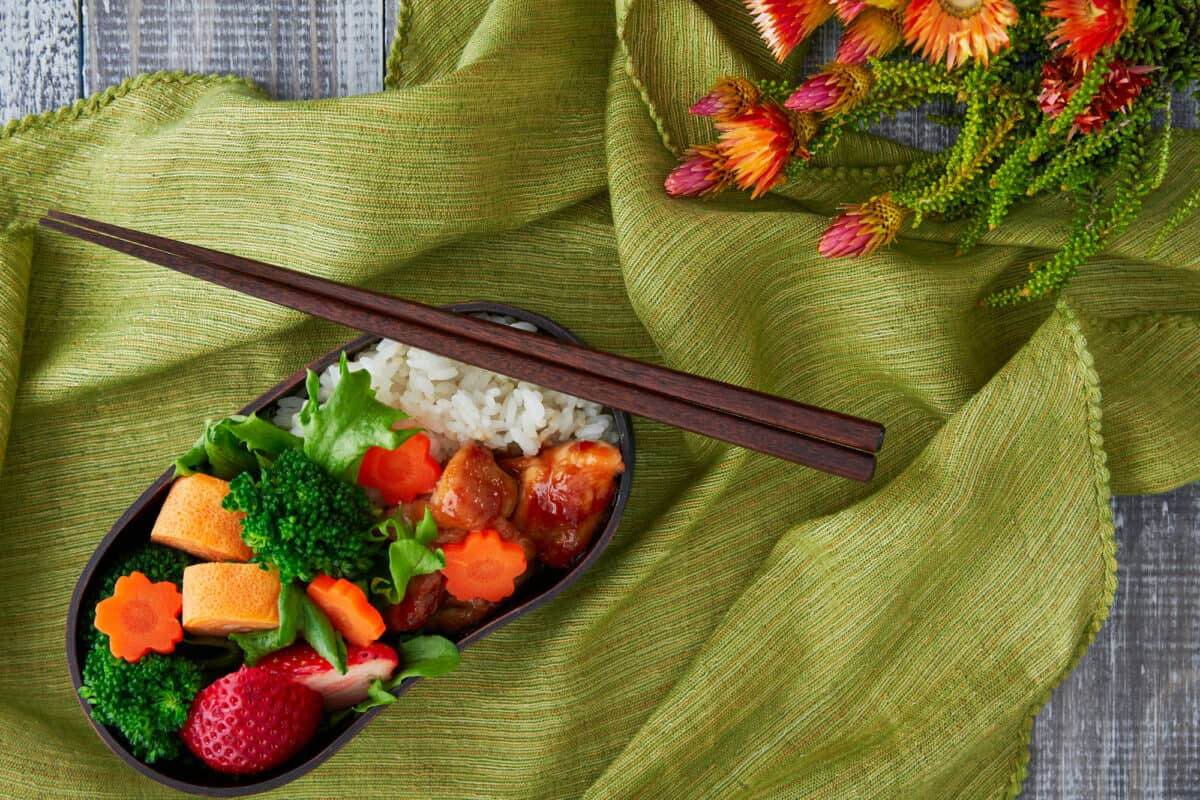 How to make and pack a traditional Japanese bento box lunch with tamagoyaki, ginger chicken, vegetables, and rice.
