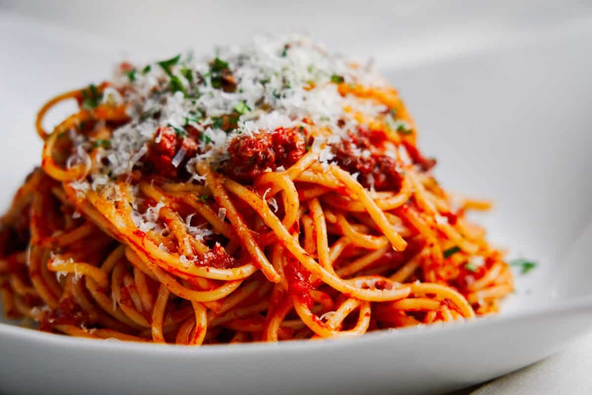 A mound of the best quick spaghetti with meat sauce dusted with parmesan cheese.