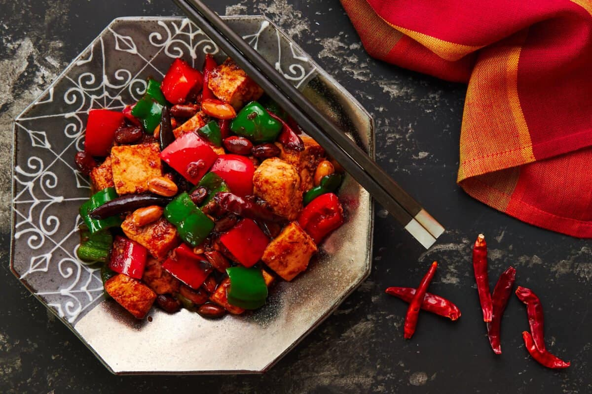Vegan Kung Pao Tofu on a silver plate with chopsticks and a red and yellow napkin.