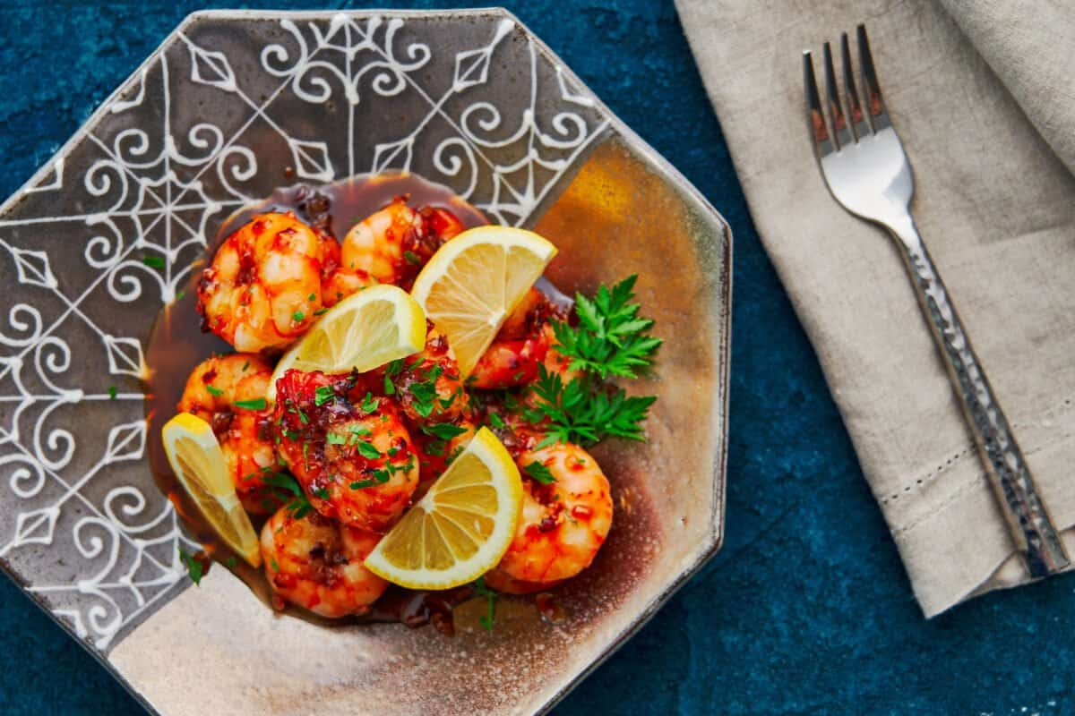 Shrimp with honey garlic sauce garnished with parsley and lemons.