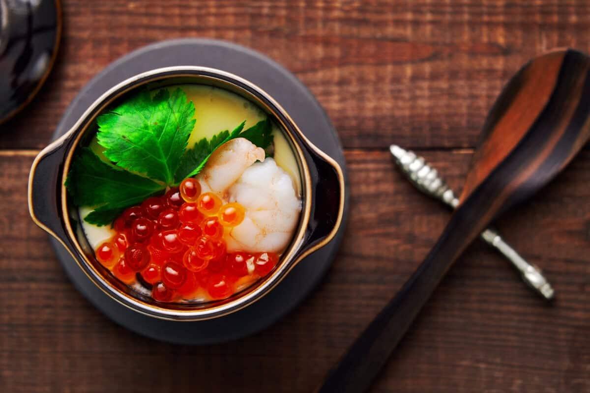 Chawanmushi (Japanese Steamed Egg) topped with ikura, shrimp, and mitsuba leaves.
