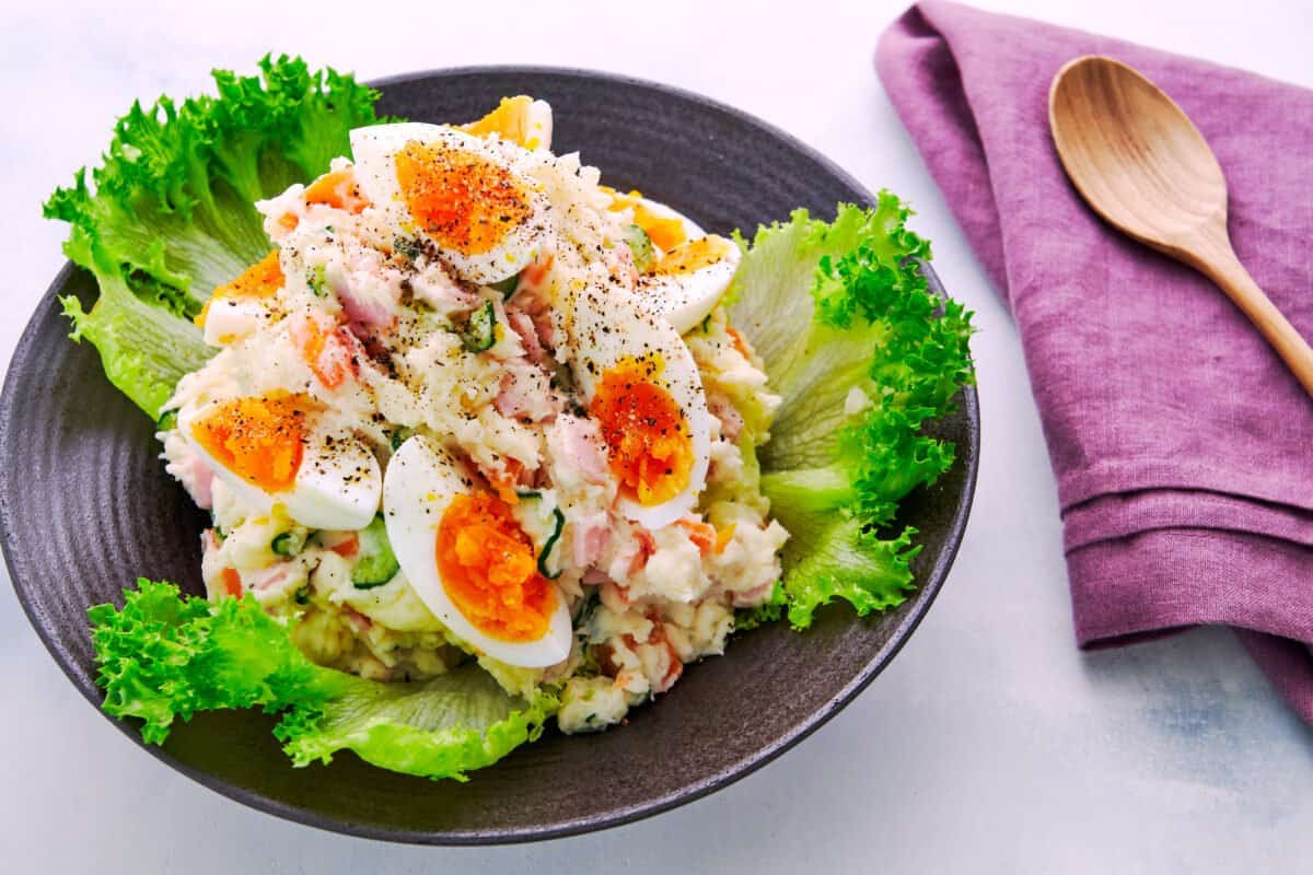 Easy, colorful Japanese Potato Salad recipe with boiled eggs, ham, cucumbers, carrots, and onions.