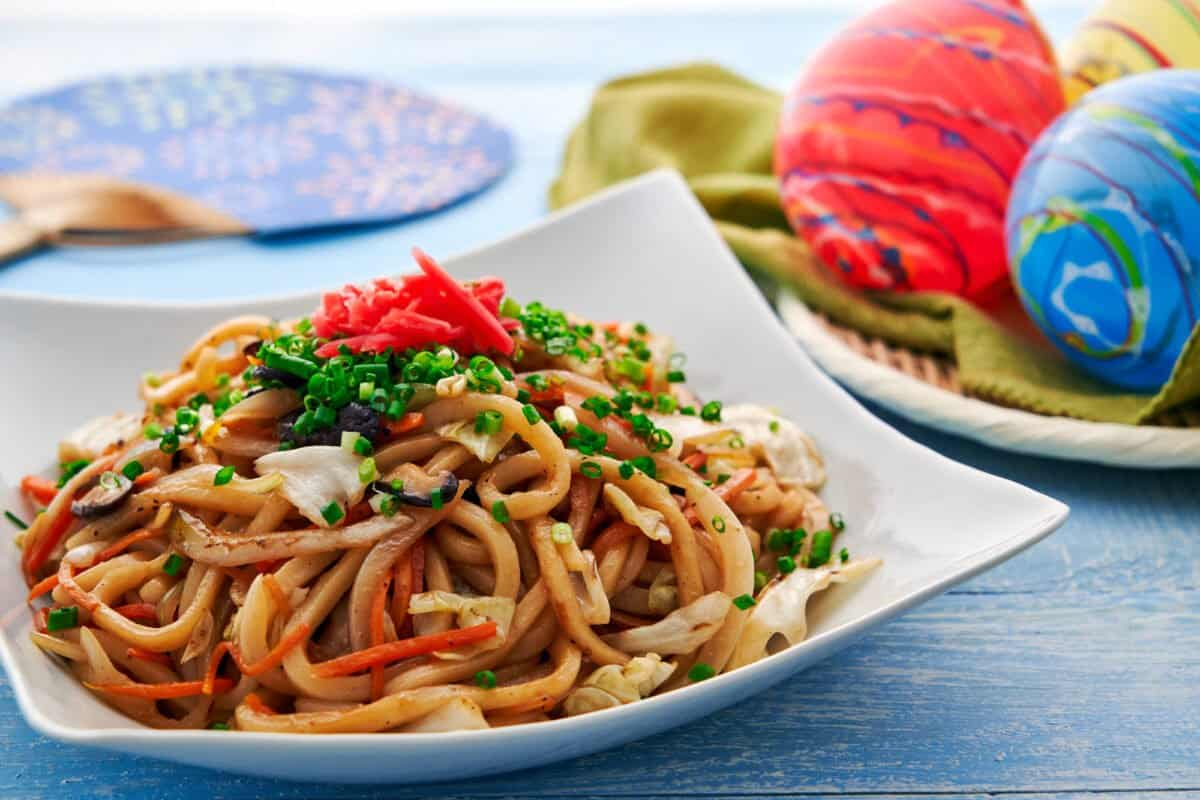 Stir-fried udon noodles with vegetables and mushrooms topped with scallions and red ginger.