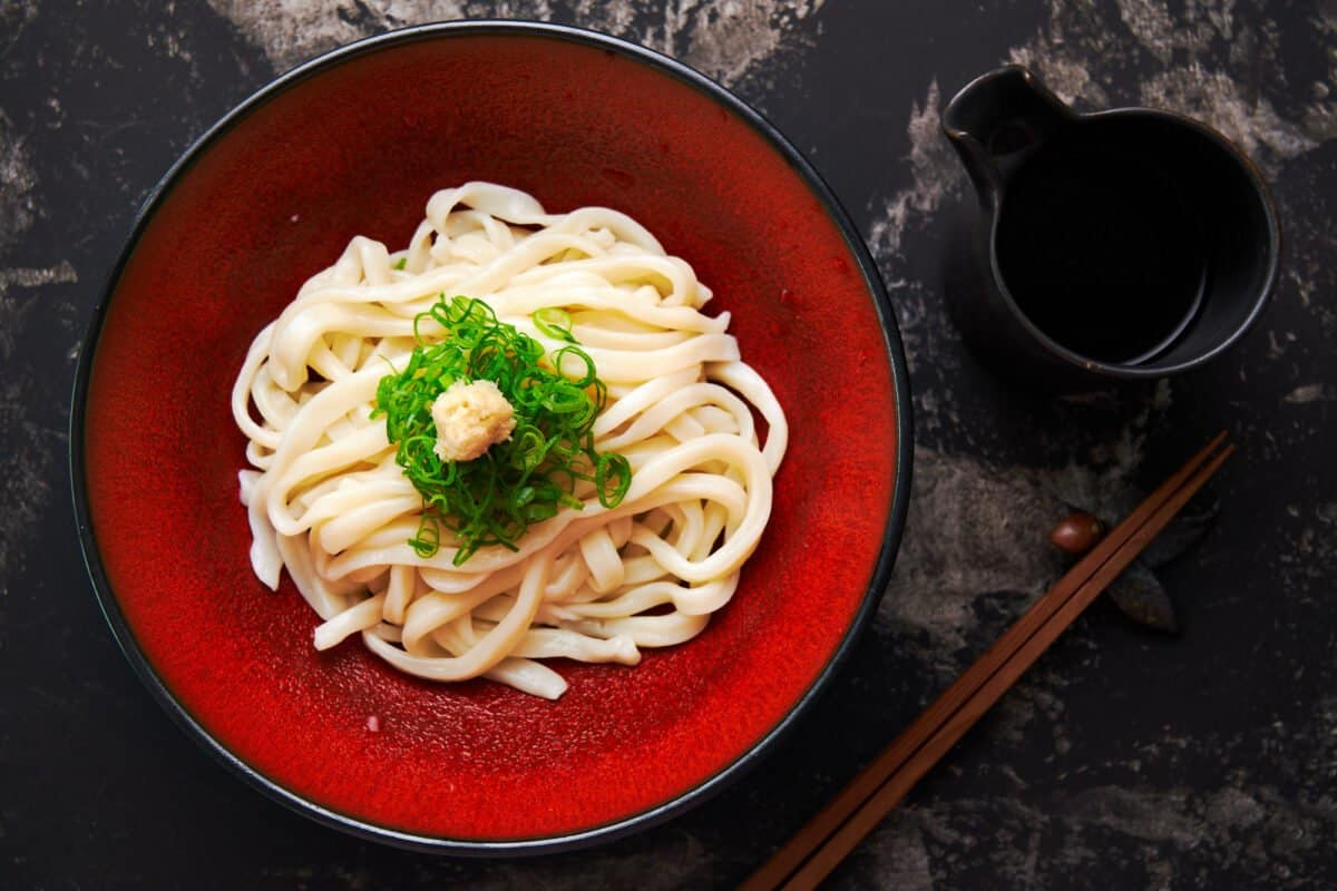 Red plate with a nest of chilled udon noodles garnished with scallions and ginger.