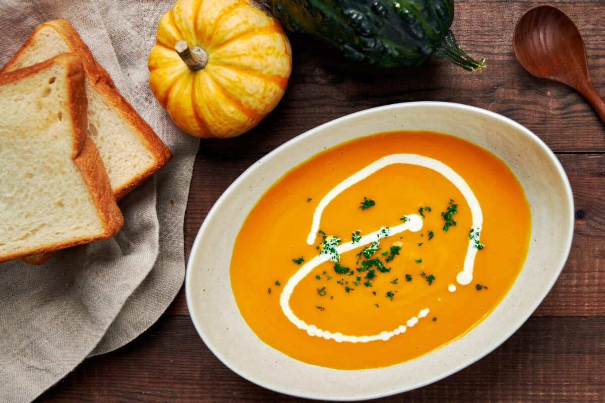 A bowl of Japanese pumpkin soup served with a drizzle of cream and a side of toast.