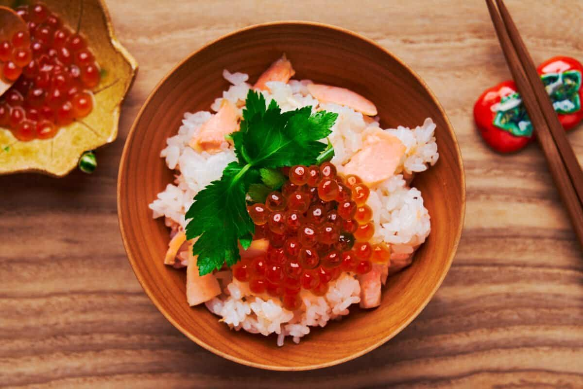 A bowl of salmon rice (salmon takikomi gohan) topped with ikura and mitsuba.