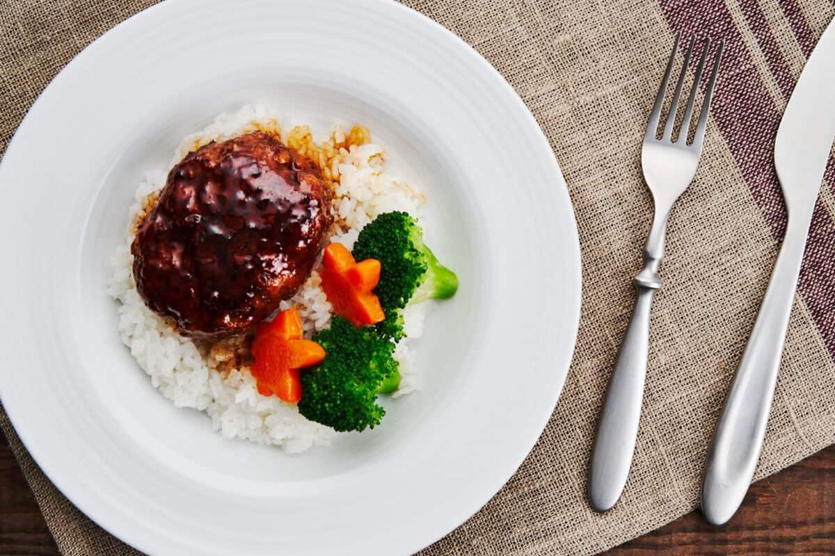 Japanese Hamburger Steak and teriyaki sauce over rice with steamed broccoli and carrots.
