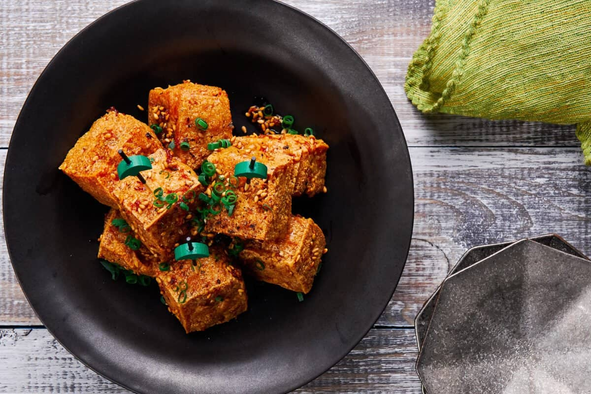Crispy tofu bites glazed in a ginger garlic sauce and topped with toasted sesame seeds, black pepper and scallions.