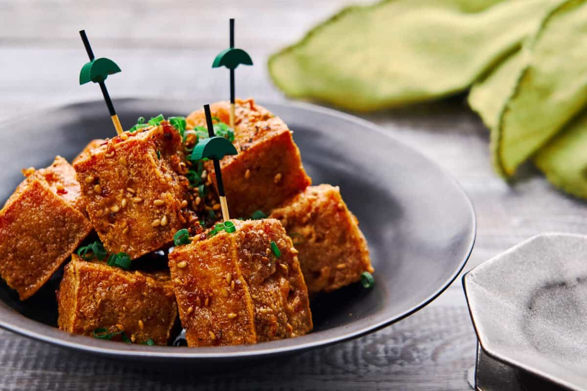 Shatteringly crisp cubes of tofu glazed in a savory-sweet ginger, garlic and black pepper sauce. A delicious plant-based canape.