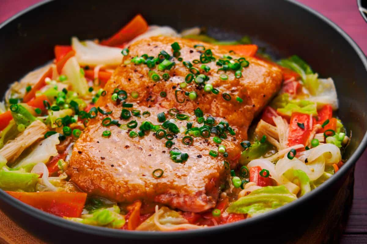 Miso butter glazed salmon steamed on a bed of sweet vegetables.