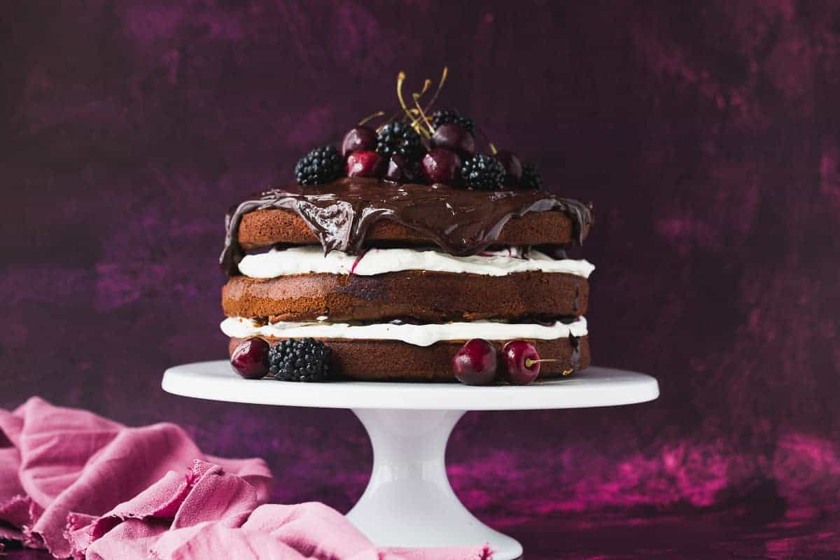 A black forest cake sitting on a white cake stand.