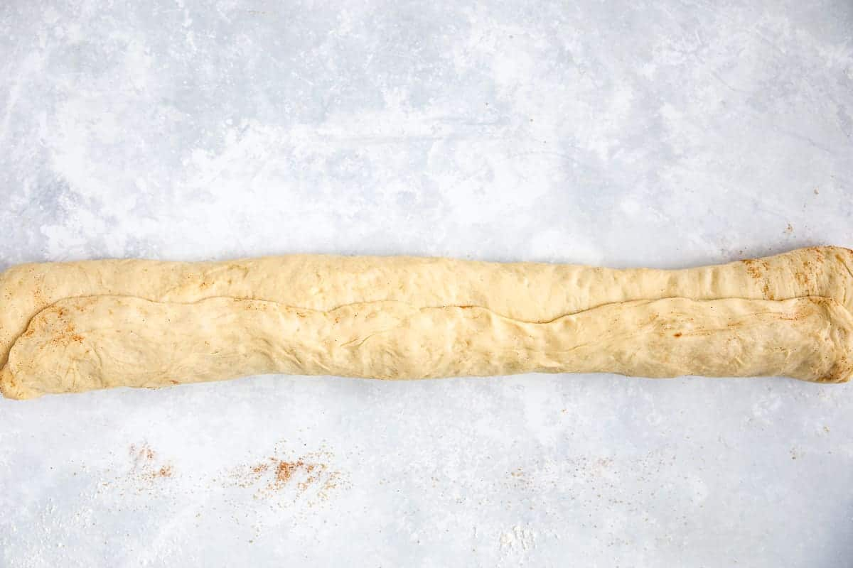 Dough that has been rolled into a sausage shape ready to be cut into individual pieces.