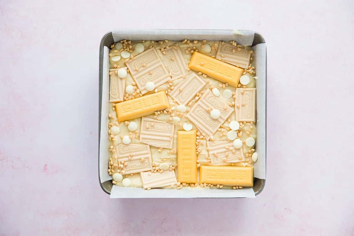 A square baking tin with a white chocolate blondie mixture. Gold bars and caramac bars have been added to the top.