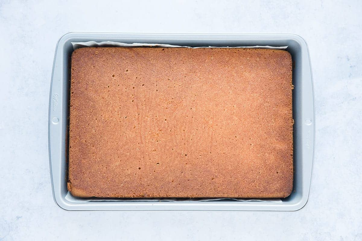 A baked cake has been flipped inside a rectangular baking tray so that the flat side is now on top. It looks a golden brown colour and has a very even texture.
