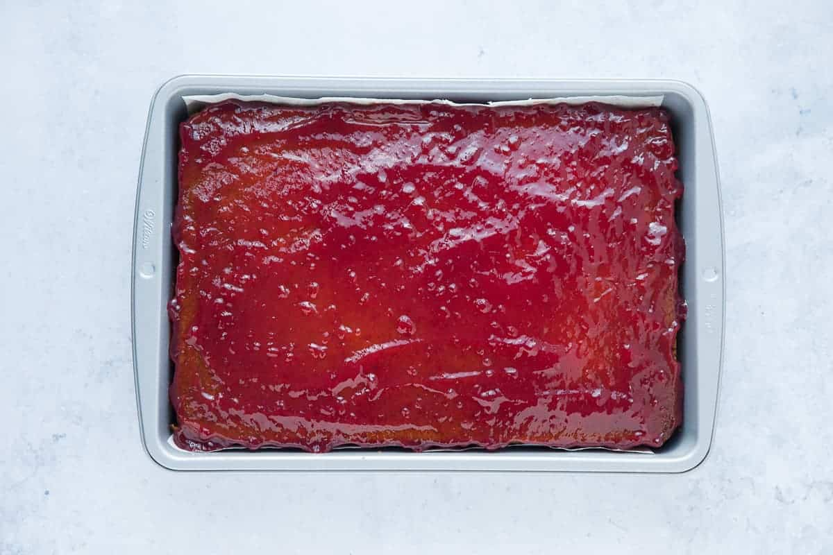 A large sponge cake that has been spread with raspberry jam.