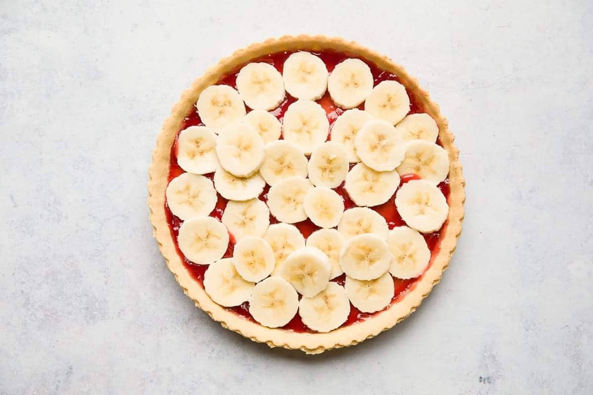 A pastry shell with a layer of jam and sliced bananas.