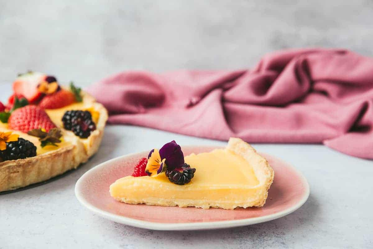 A slice of French lemon pie on a pink plate.